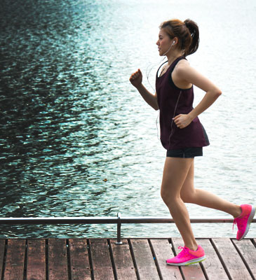 Young lady jogging by the water
